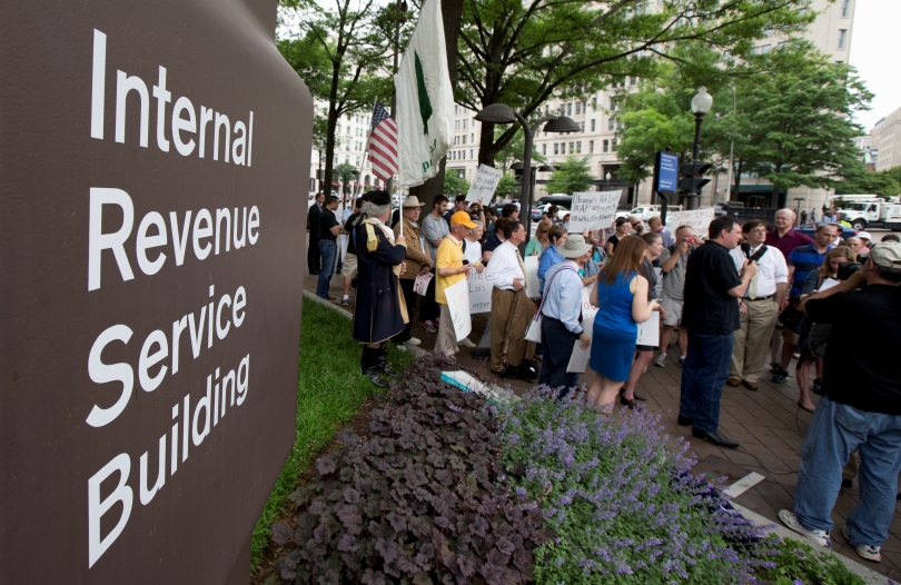 Tea Party supporters gather for a rally outside the IRS headquarter in Washington, May 21, 2013. A few dozen tea party activists and their supporters have gathered outside the IRS headquarters in Washington to protest extra scrutiny of their organizations. (AP Photo/Manuel Balce Ceneta)